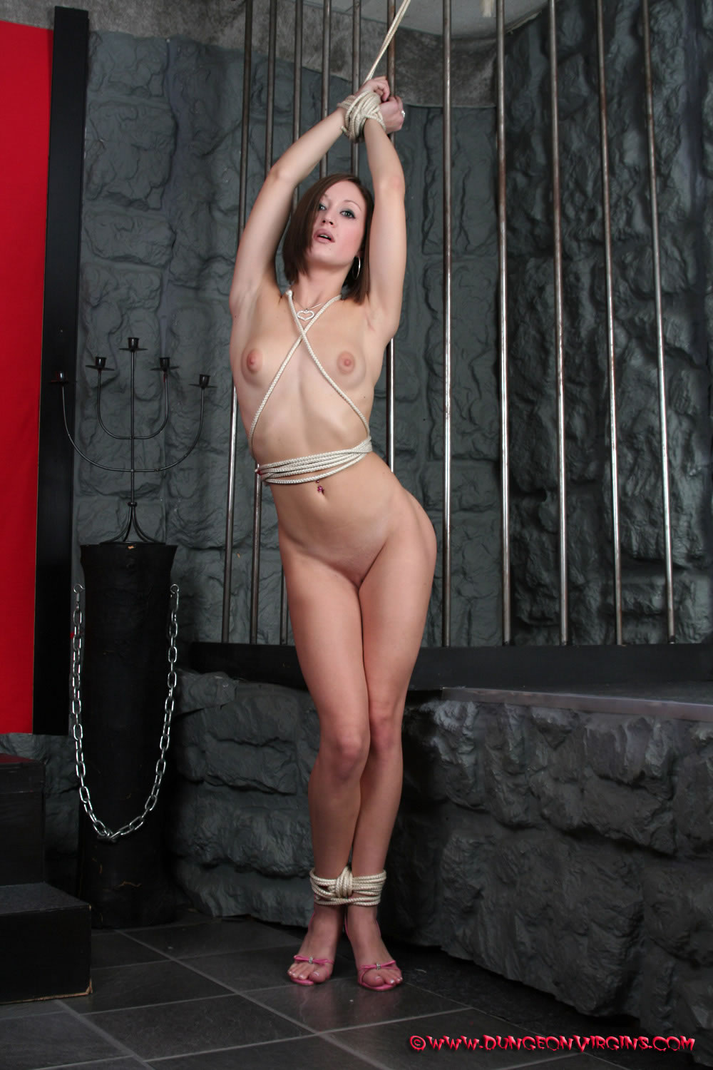 Full length side view of nude aerial dancer with red silk ropes